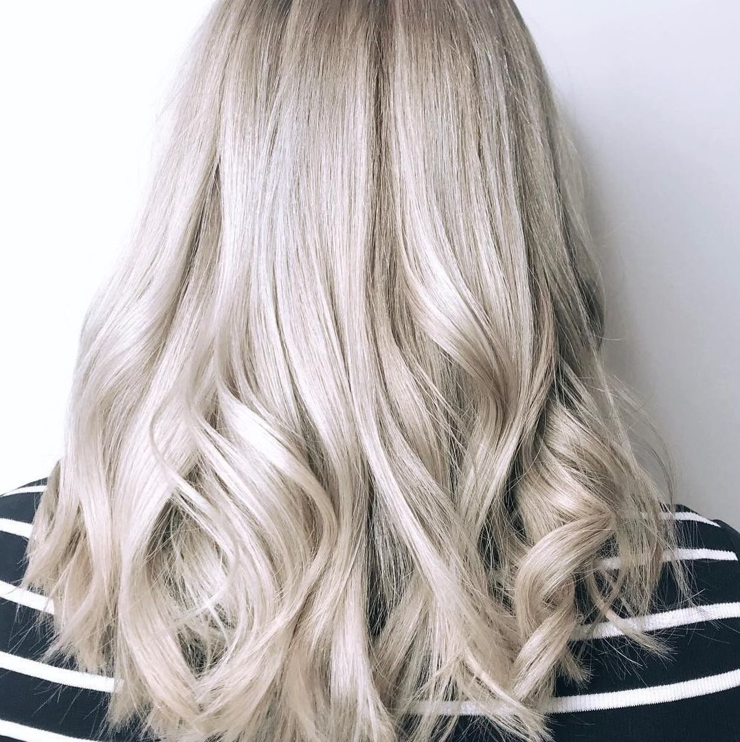 Woman with long wavy ice blonde hair using Koleston Perfect