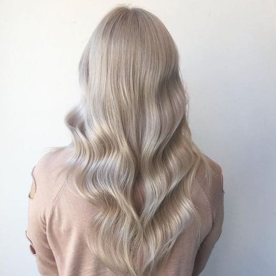 Woman with long wavy ice blonde hair using Blondor Powder