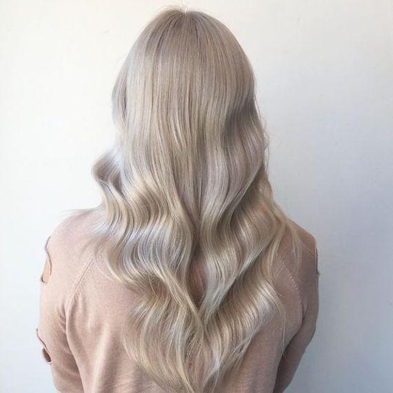 Woman with long wavy ice blonde hair using Blondor Powder