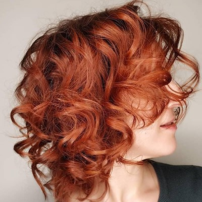 Woman with curly leather red hair, created using Wella Professionals