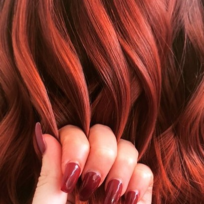 Fingers holding wavy leather red hair, created using Wella Professionals