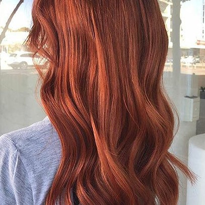 Woman with wavy leather red hair, created using Wella Professionals