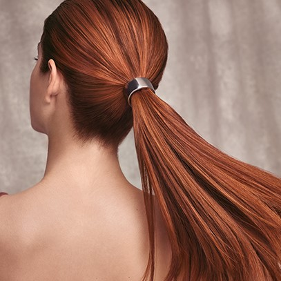 Woman with a pony tail of leather red hair, created using Wella Professionals