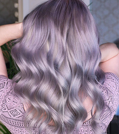 Back of woman's head with mid-length, wavy, pastel lilac hair, created using Wella Professionals