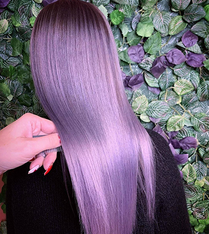 Back of woman's head with long, straight, glossy violet hair, created using Wella Professionals.