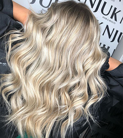 Back of womans head with curled soft blonde hair