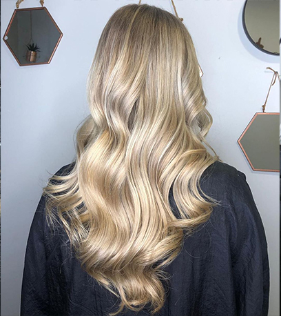 Back of womans head with curled satin blonde hair