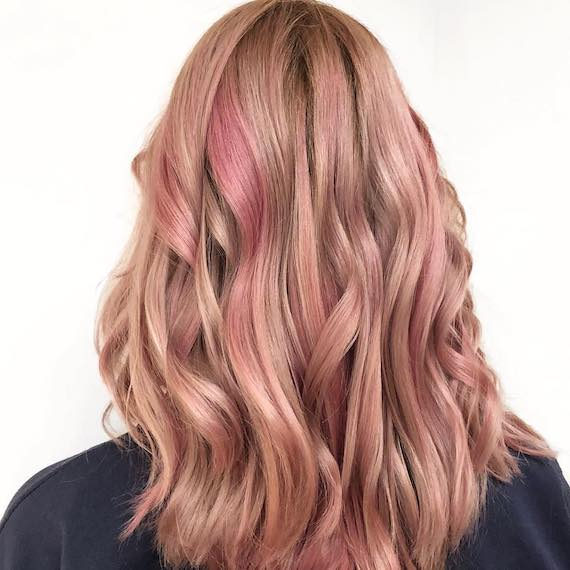 Model with long, wavy hair and strawberry highlights, created using Wella Professionals.