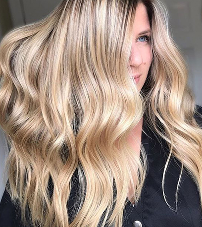 Woman with wavy, sandy blonde hair, created using Wella Professionals.