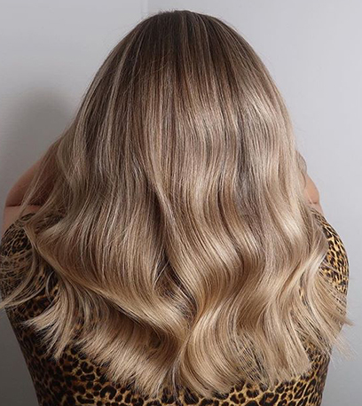 Back of woman's head with wavy, sandy blonde hair, created using Wella Professionals.