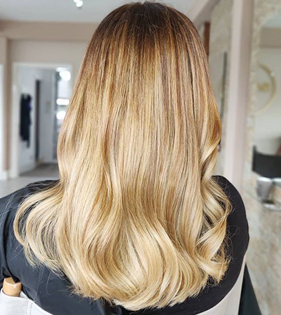 Back of woman's head with long, loosely curled, sandy blonde hair, created using Wella Professionals.