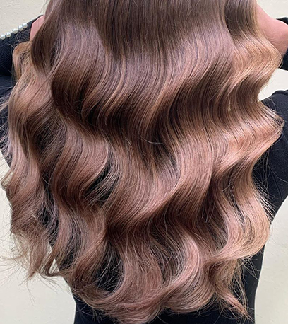 Back of woman's head with ultra-glossy, loosely curled, brown sombre hair, created using Wella Professionals.
