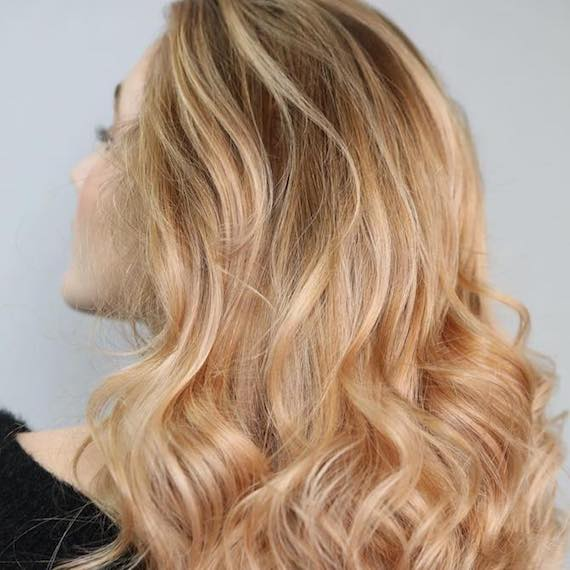 Back of a woman's head showing long wavy, copper peach hair, created using Wella Professionals.