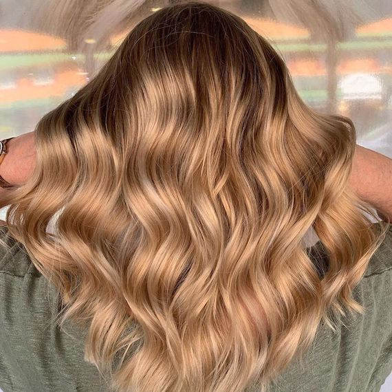 Back of a woman's head showing long wavy, faded strawberry blonde hair, created using Wella Professionals.