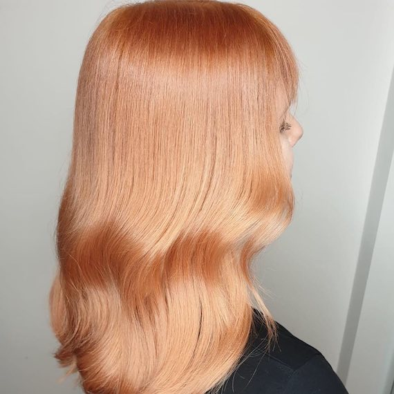 Back of a woman's head showing long, peachy blonde hair, created using Wella Professionals.
