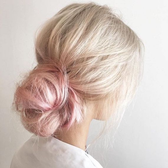 Model with blonde hair and pink tips pulled into a low bun, created using Wella Professionals.