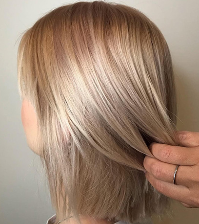 Model with straight hair and subtle pink highlights, created using Wella Professionals.