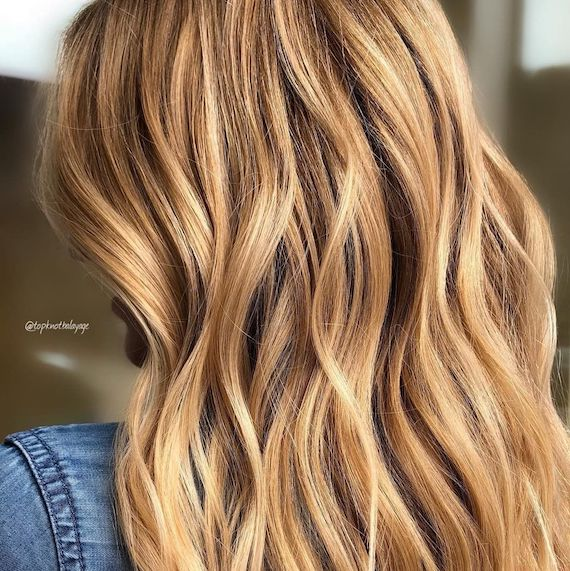 Model with long wavy hair in warm blonde and highlights created with Blondor Freelights and Color Touch