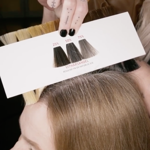 Wella Professionals colorist using the shade selector to determine the volume of gray hairs.